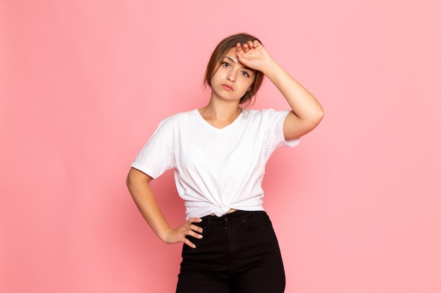 A front view young beautiful female in white shirt with posing with tired expression