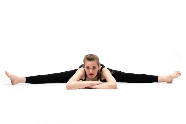 Una giovane ragazza bella vista frontale in camicia sportiva fiammata nera e pantaloni neri in posa facendo ginnastica in diverse pose sul bianco
