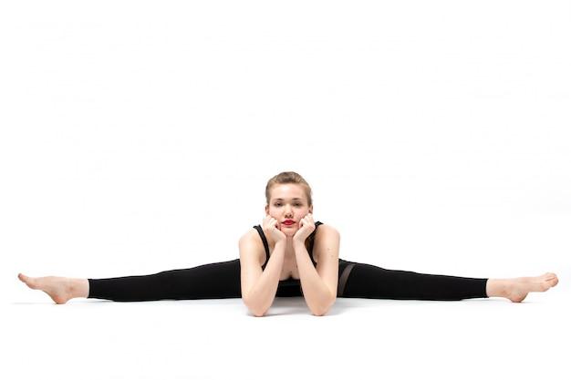 Una giovane bella ragazza di vista frontale in camicia sportiva fiammata nera e pantaloni neri che posano facendo ginnastica sul bianco