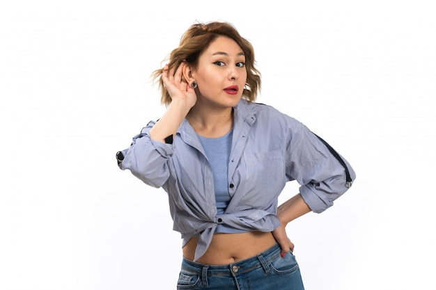 A front view young beautiful girl in blue shirt and blue jeans trying to hear out posing