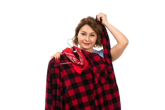 Una giovane bella ragazza di vista frontale in maglietta blu e blue jeans che tengono camicia a quadretti rosso-nera che sorride sul bianco