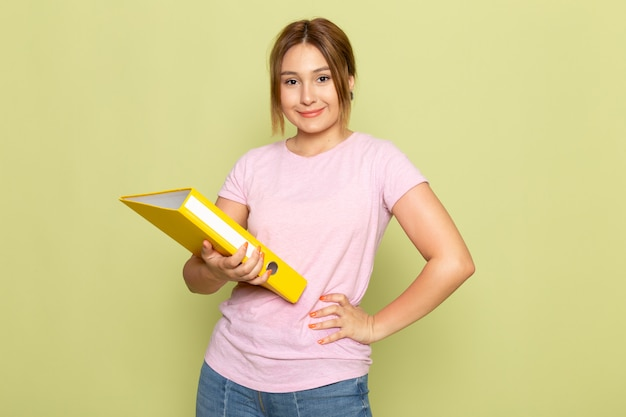 A front view young beautiful girl in pink t-shirt blue jeans posing and smiling with yellow file on green
