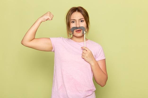 Una giovane bella ragazza di vista frontale in blue jeans della maglietta rosa che posa con i baffi falsi e che flette sul verde