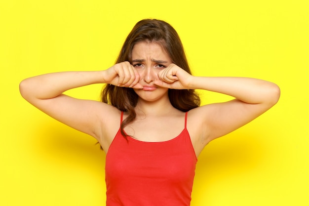 A front view young beautiful girl in red shirt and blue jeans posing with crying expression