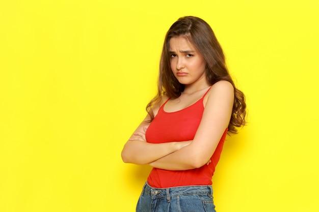 Una giovane bella ragazza di vista frontale in camicia e blue jeans rosse che posano con l'espressione pazza e rattristata