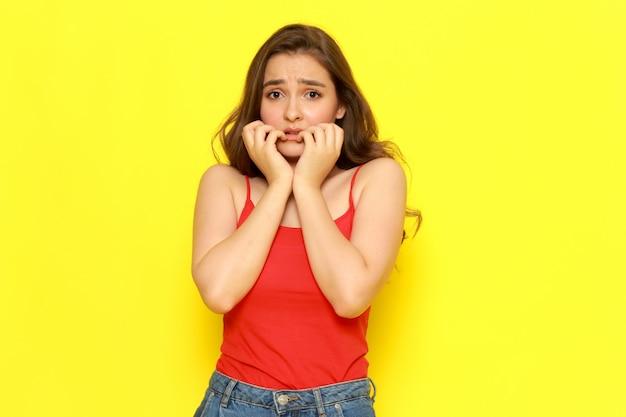 Una giovane bella ragazza di vista frontale in camicia e blue jeans rosse che posano con l'espressione spaventata