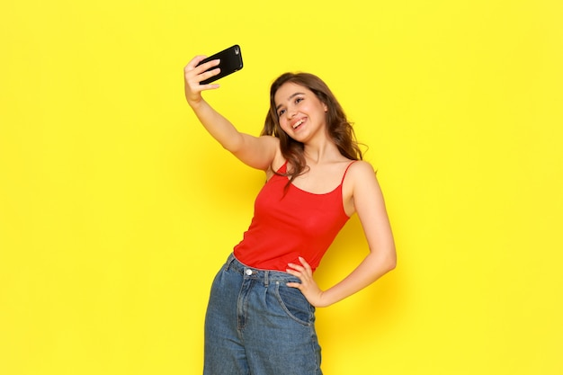 A front view young beautiful girl in red shirt and blue jeans taking a selfie