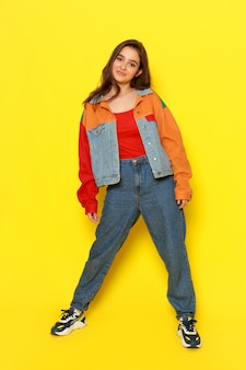 A front view young beautiful girl in red shirt coat and blue jeans posing with smiling expression