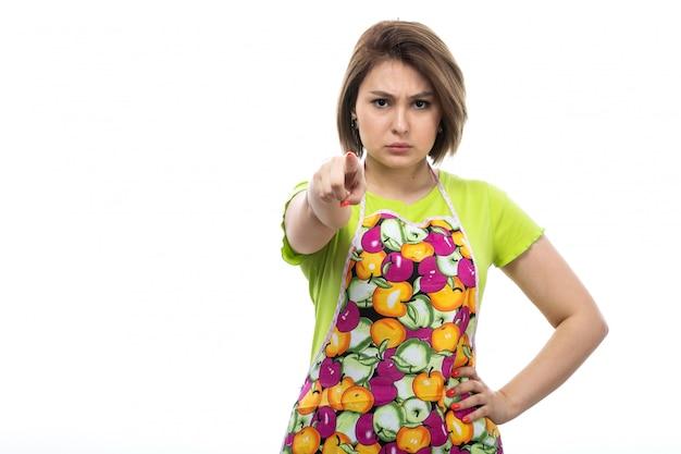Una giovane bella casalinga di vista frontale nell'espressione arrabbiata del capo variopinto della camicia verde sulla cucina bianca della femmina della casa del fondo