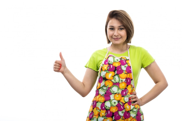 A front view young beautiful housewife in green shirt colorful cape posing showing awesome sign smiling on the white background house female kitchen