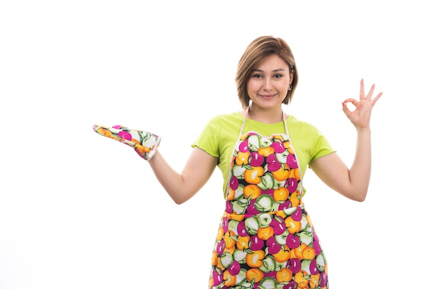 A front view young beautiful housewife in green shirt colorful cape posing smiling on the white background house cleaning kitchen