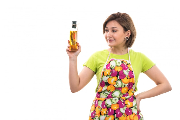 A front view young beautiful housewife in green shirt colorful cape smiling holding bottle with oil on the white background house cleaning kitchen