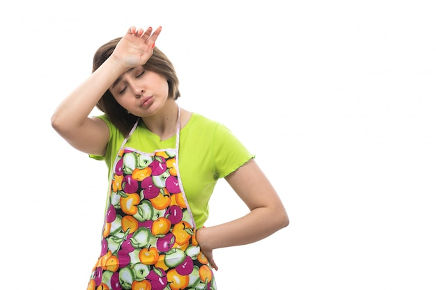 A front view young beautiful housewife in green shirt colorful cape tired exhausted due to housework