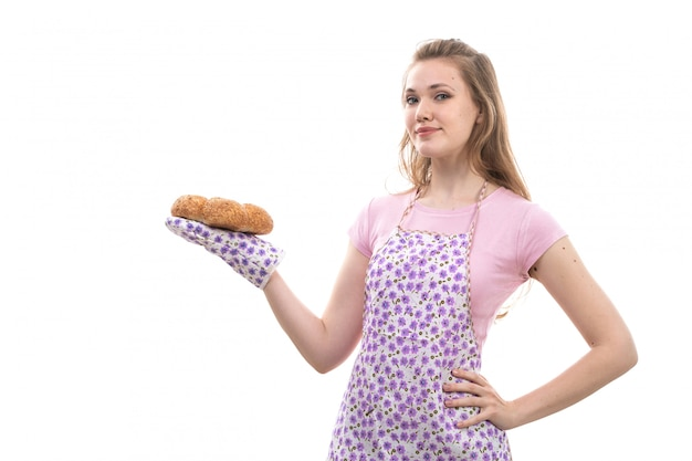 Una giovane bella casalinga di vista frontale nel sorridere sorridente felice delle panetterie della tenuta del capo variopinto variopinto della camicia rosa