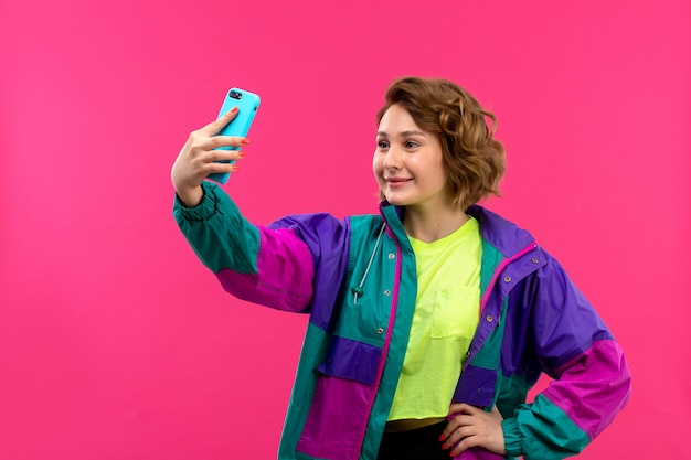 A front view young beautiful lady in acid colored shirt black trousers colorful jacket taking selfie smiling