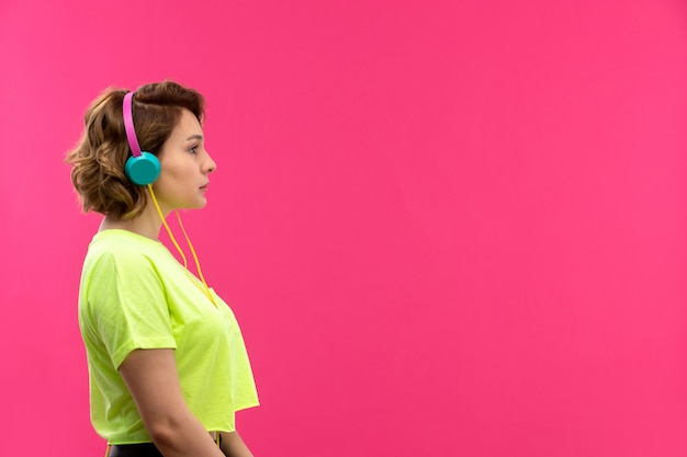 A front view young beautiful lady in acid colored shirt black trousers listening to music in blue earphones