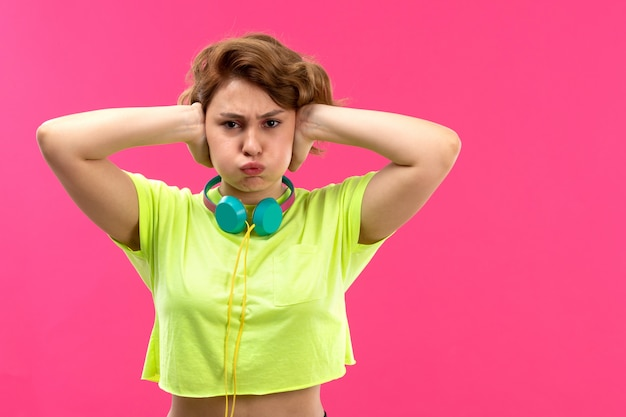 A front view young beautiful lady in acid colored shirt black trousers with blue earphones displeased