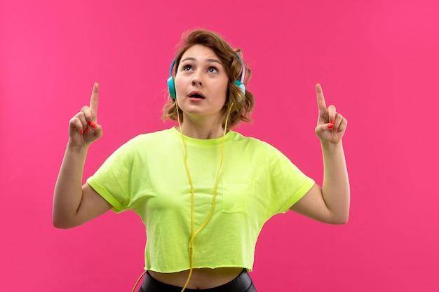 Una vista frontale giovane bella signora in pantaloni neri camicia color acido con auricolari blu ascoltando la speranza di musica