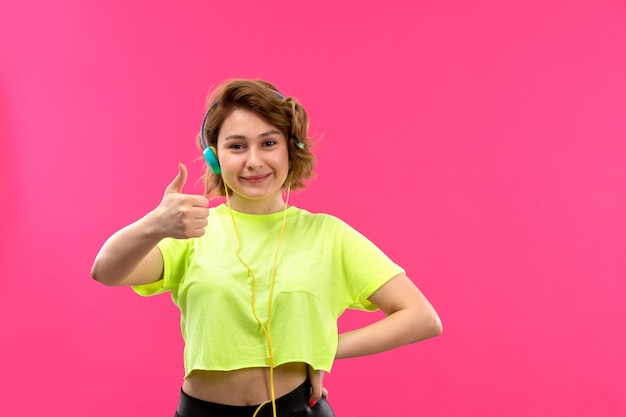 Una giovane donna bella vista frontale in pantaloni neri di camicia color acido con auricolari blu ascoltando musica sorridente felice