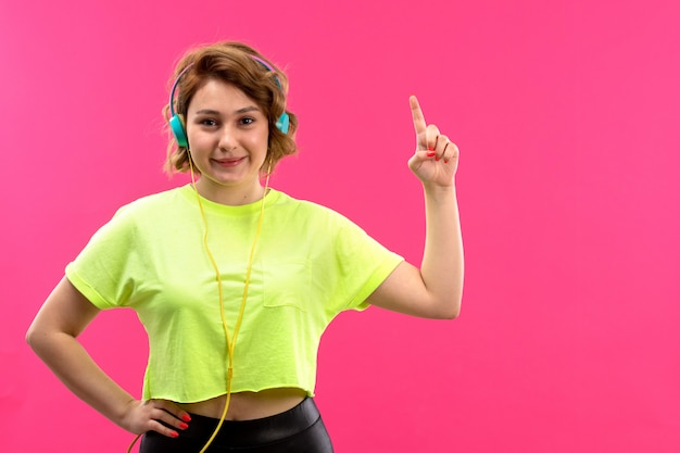 A front view young beautiful lady in acid colored shirt black trousers with blue earphones listening to music smiling