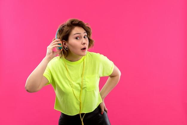 Una vista frontale giovane bella signora in camicia di colore acido pantaloni neri con auricolari blu ascoltando musica cercando di ascoltare