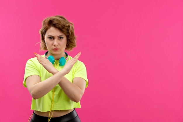 A front view young beautiful lady in acid colored shirt black trousers with blue earphones showing banned sign