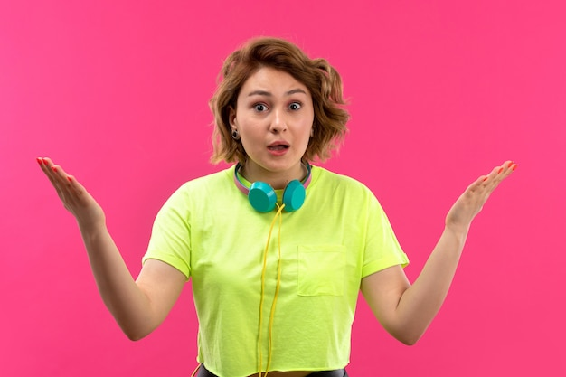 A front view young beautiful lady in acid colored shirt black trousers with blue earphones suprised