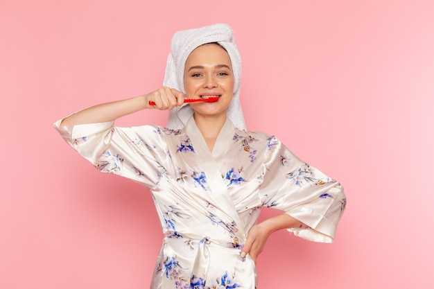A front view young beautiful lady in bathrobe cleaning her teeth