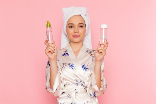 Una giovane donna bella vista frontale in accappatoio detenzione spray detergente per il trucco con il sorriso sul suo viso
