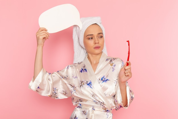 A front view young beautiful lady in bathrobe holding white sign and toothbrush