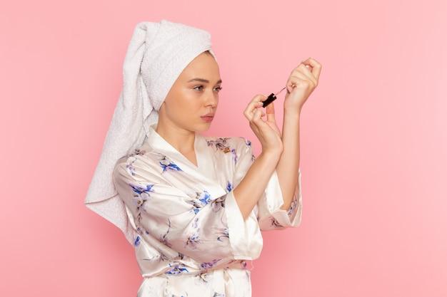 Una giovane donna bella vista frontale in accappatoio dipinto le unghie