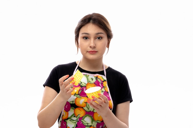 A front view young beautiful lady in black shirt and colorful cape holding yellow little cake pans