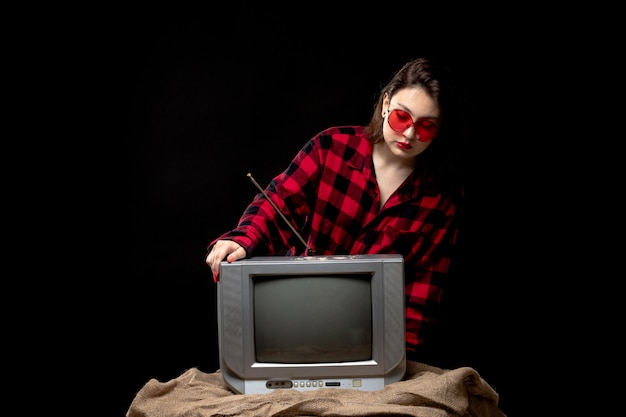 A front view young beautiful lady in checkered red-black shirt in red sunglasses near little tv