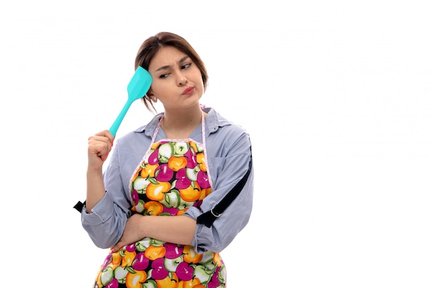 A front view young beautiful lady in light blue shirt and colorful cape thinking holding blue kitchen appliance