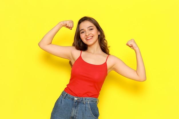 Una giovane bella signora di vista frontale in camicia rossa e blue jeans che flettono e che sorridono