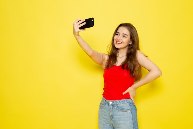 A front view young beautiful lady in red shirt and blue jeans taking a selfie