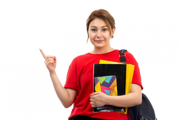 A front view young beautiful lady in red t-shirt black jeans holding different copybooks and files smiling with bag on the white