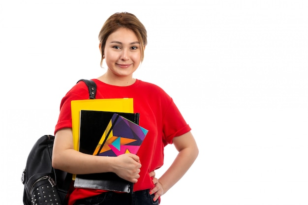 A front view young beautiful lady in red t-shirt black jeans smiling holding different copybooks and files with bag on the white