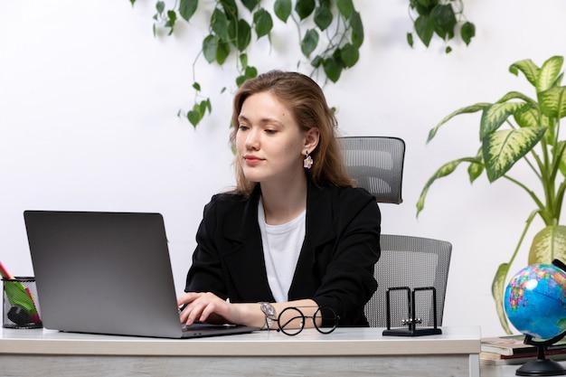 Una giovane donna bella vista frontale in camicia bianca e giacca nera, lavorando con documenti usando il suo computer portatile davanti al tavolo con foglie appese
