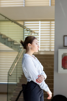 A front view young beautiful lady in white shirt black trousers looking at the distance in the hall waiting during daytime building job activity