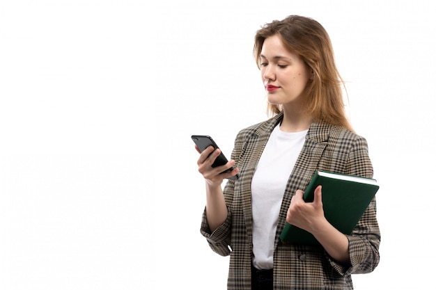 A front view young beautiful lady in white t-shirt black jeans and coat holding black smartphone and green book on the white