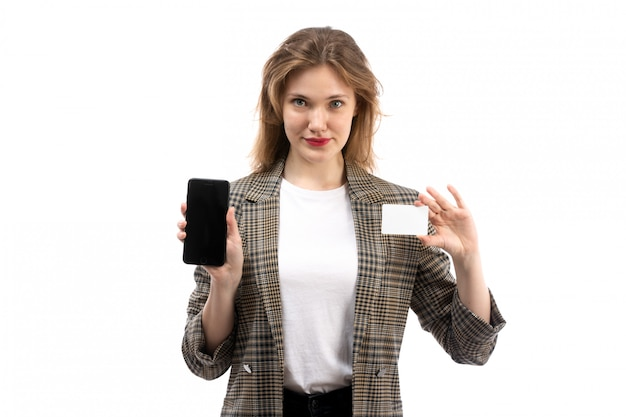 A front view young beautiful lady in white t-shirt black jeans and coat holding black smartphone and white card on the white