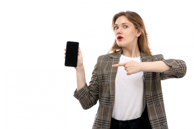 A front view young beautiful lady in white t-shirt black jeans and coat holding showing smartphone on the white
