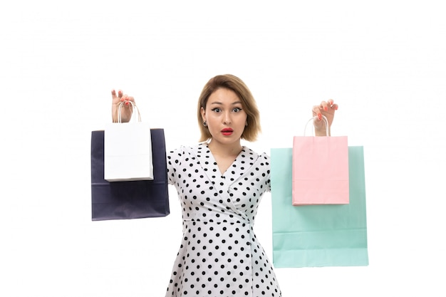 A front view young beautiful woman in black-and-white polka dot dress holding shopping packages posing shocked expression
