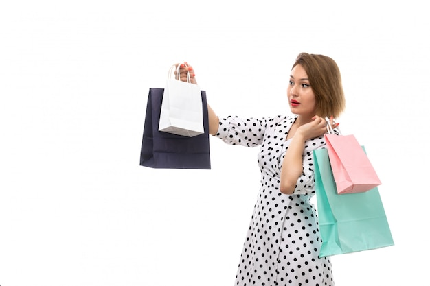 A front view young beautiful woman in black-and-white polka dot dress holding shopping packages surprised