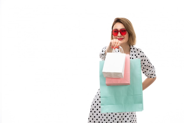 A front view young beautiful woman in black-and-white polka dot dress in red sunglasses holding shopping packages posing