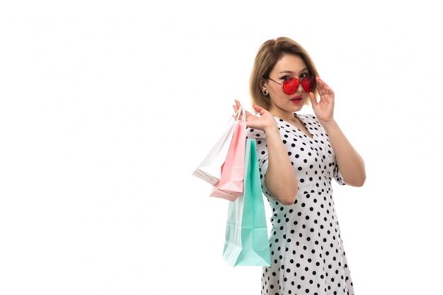 Una giovane bella donna di vista frontale in vestito a pois in bianco e nero in occhiali da sole rossi che tengono posa dei pacchetti di acquisto