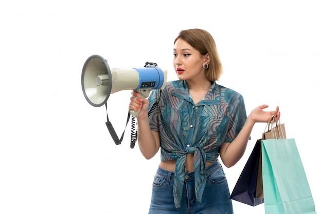 A front view young beautiful woman in colored blouse blue jeans holding shopping packages using megaphone