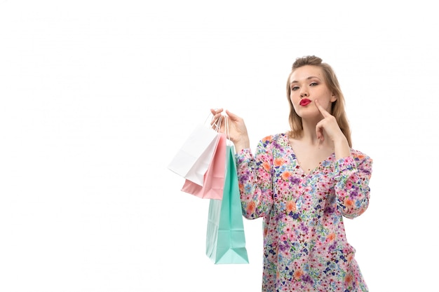 A front view young beautiful woman in flower designed shirt and black trousers holding shopping packages posing