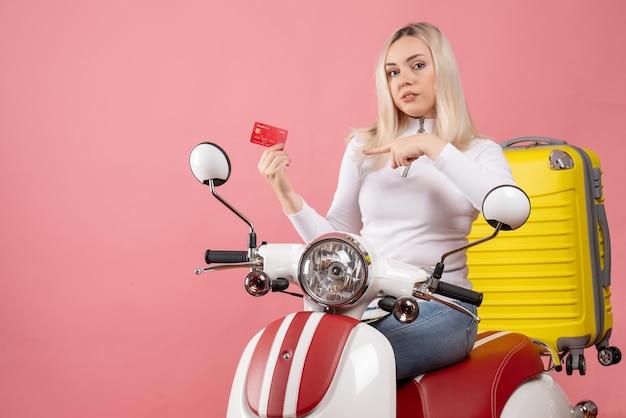 카드에서 가리키는 오토바이에 전면보기 젊은 금발 소녀